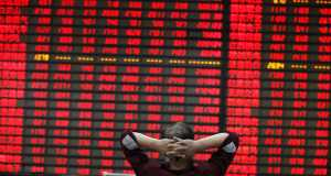 Investor watchs electric board in a stock market. China fund. Chinese equities.